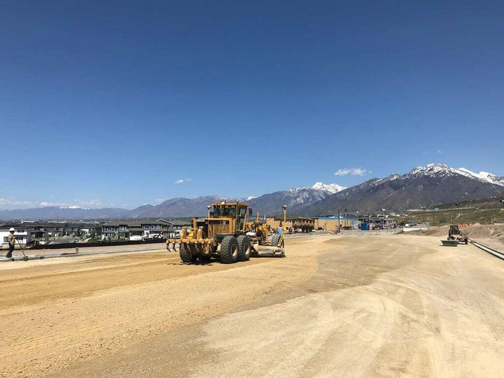 Grading road base material before paving Porter Rockwell Blvd.